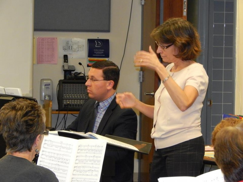 Jodi Rinehimer leading choral directors in a reading session, while Michael O'Malley accompanies